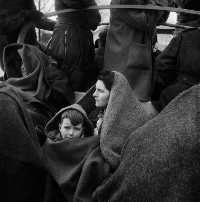 Het jongetje Iek met zijn broer en zus onder de deken bij zijn moeder opschoot in de DUKW, Stavenisse (1953). © Ed van WijkNederlands Fotomuseum