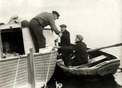 Parlevinker. De melkboer bezorgt flessen melk aan boord van een schip. Foto 1930.